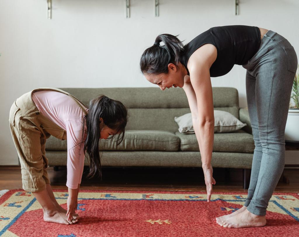 a mom and her daughter exercise indoors while having fun